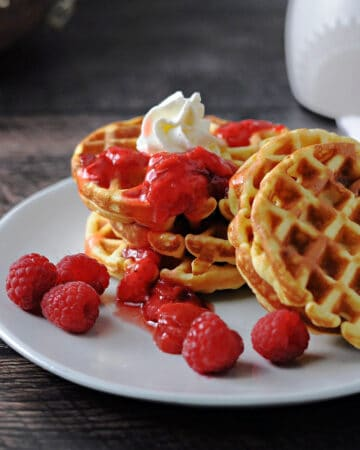 stack of 4 keto waffles (breakfast chaffles)with a little berry sauce drizzled on top and a dollop of whipped cream. 2 palin waffles lean on teh stack and some raspberries are also scattered on the plate