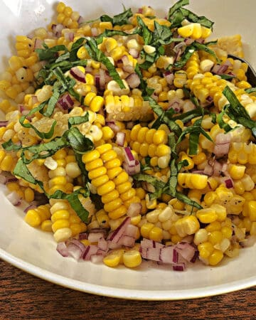 up close of corn salad in a white bowl