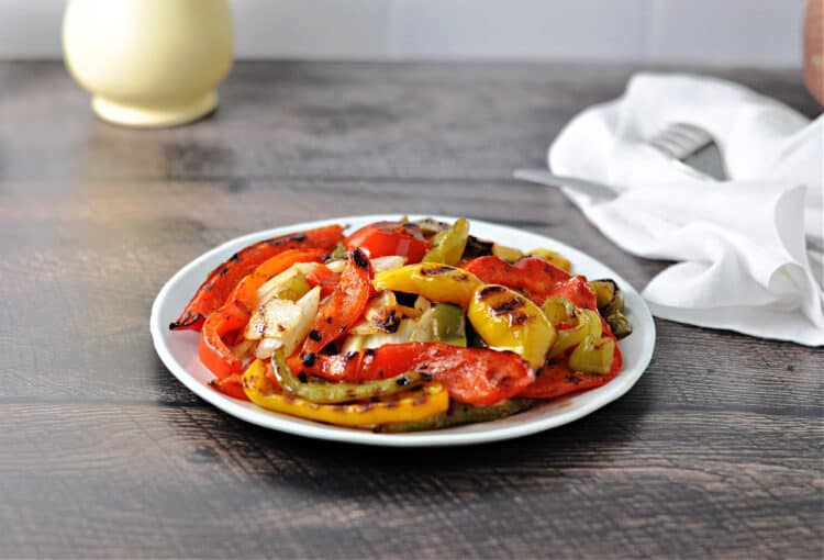 grilled onions and peppers on a small white plate