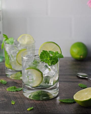 Bacardi mojito in a glass with ice, mint and limes. a second mojito is behind the first.