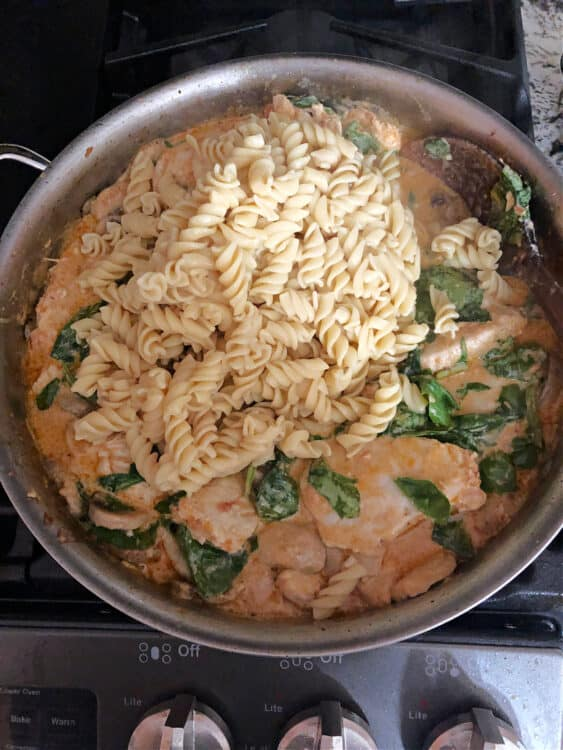 adding noodles to the pan of sauce