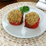 2 grilled stuffed tomatoes on a small white plate