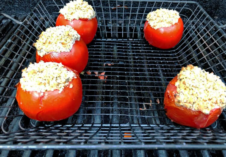 stuffed tomatoes in a grill basket on the grill