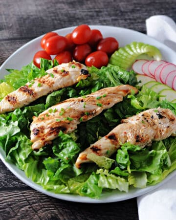 3 grilled chicken tenders on a bed of greens surrounded by salad ingredients
