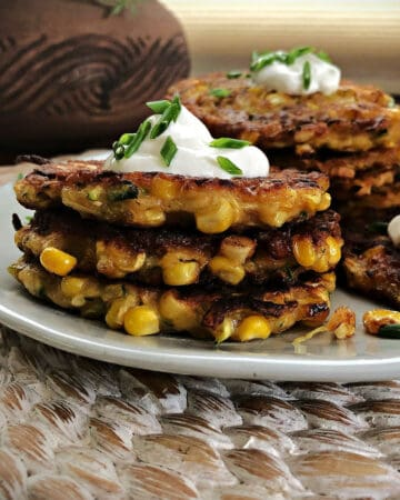 zucchini corn fritters stacked on a plate