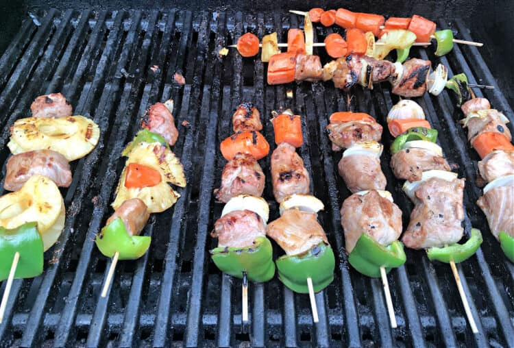Sweet and sour pork kabobs cooking on the grill