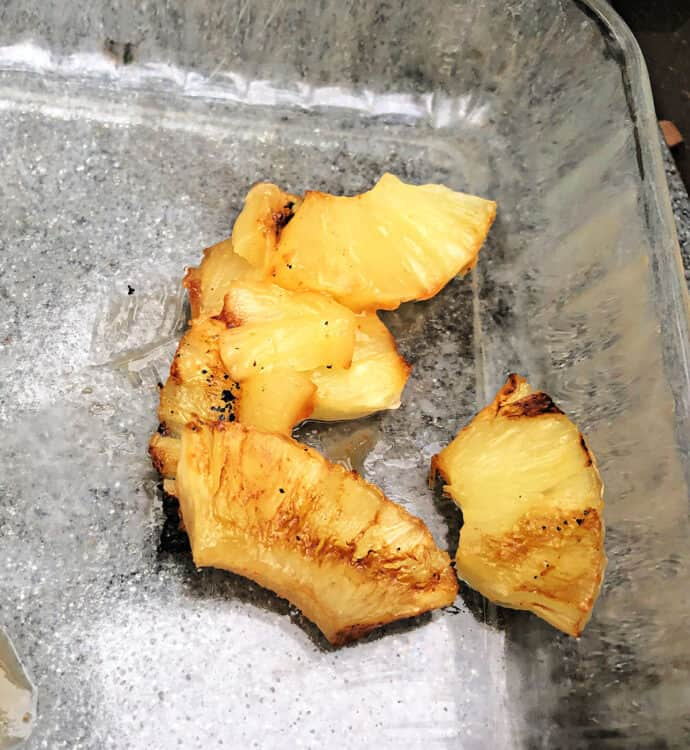 chunks of grilled pineapple falling apart in a glass pan