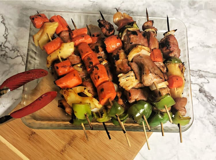 Sweet and sour pork kabobs grilled and stacked in a glass pan