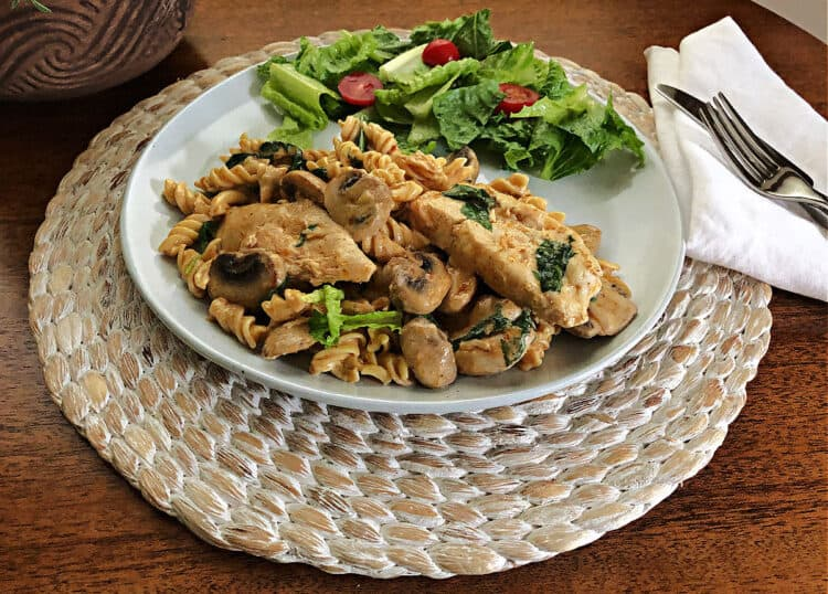 sun dried tomato pesto chicken on a plate with a side salad