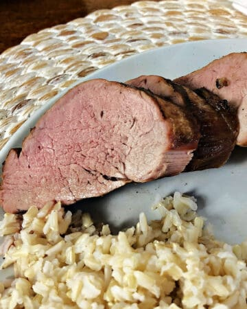 pork tenderloin slices on a white plate with rice