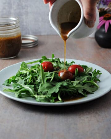 small pitcher pouring balsamic vinaigrette onto a plate of salad greens