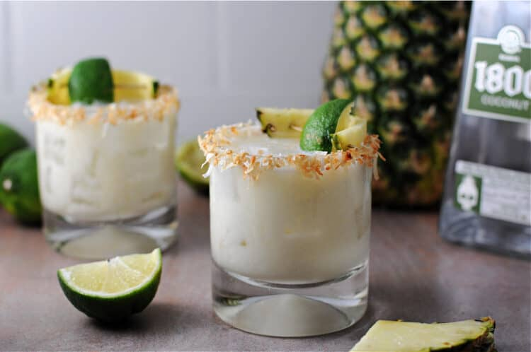 2 coconut pineapple margaritas garnished with a rim of toasted coconut. lime wedges and a whole fresh pineapple surround the area.