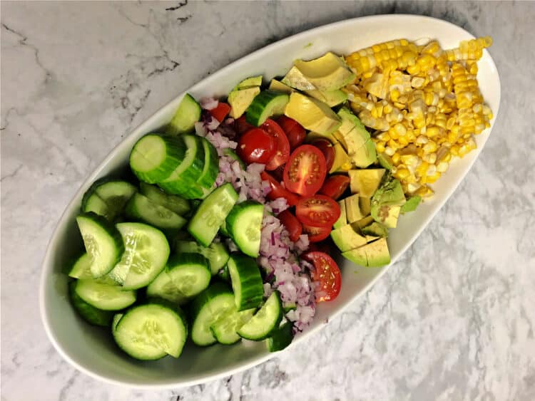 Bowl of separate ingredients: corn, avocado, tomatoes, onion, cucumber