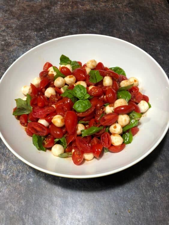 grape tomato mozzarella salad, top down image in a white bowl