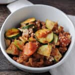 zucchini ground beef casserole in a small white bowl sitting on a white napkin