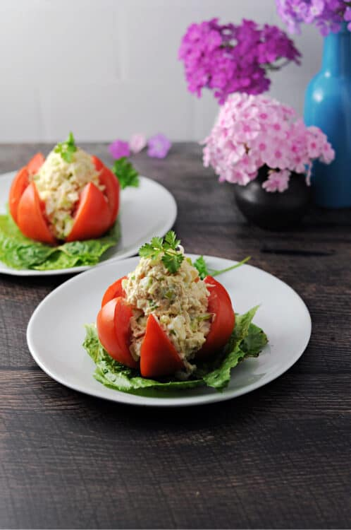 tuna stuffed tomato on a small plate, second serving behind it as well as flowers in a vase