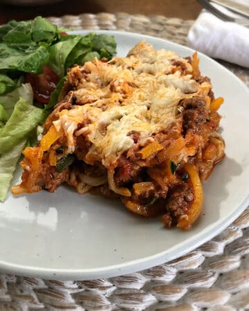butternut squash spaghetti bake in a white plate with salad