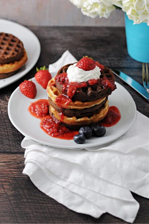 stack of cake mix waffles with fruit sauce and whipped cream on top
