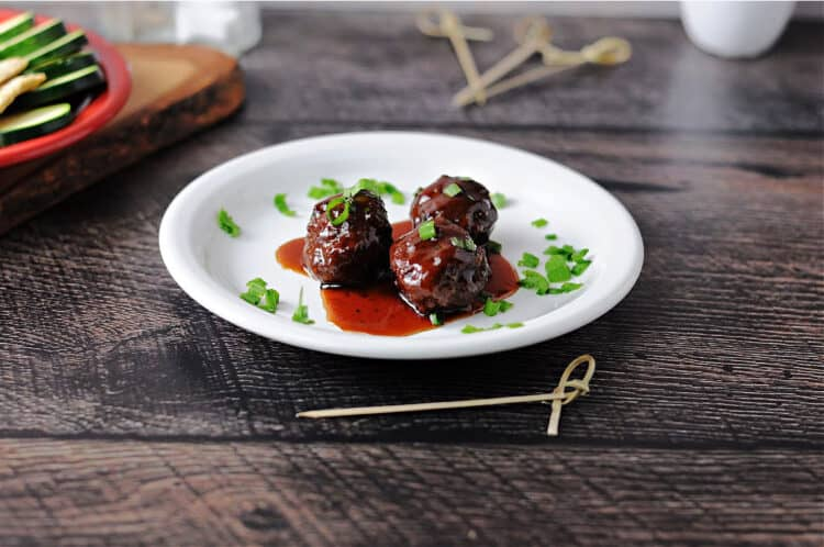 3 grape jelly bbq meatballs on a small white plate with sauce pooling around them