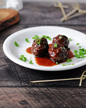 grape jelly bbq meatballs on a small white plate