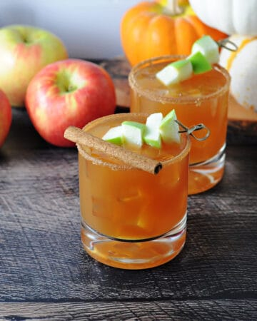 2 caramel apple cider vodka drinks garnished with apple cubes and cinnamon, whole apples behind