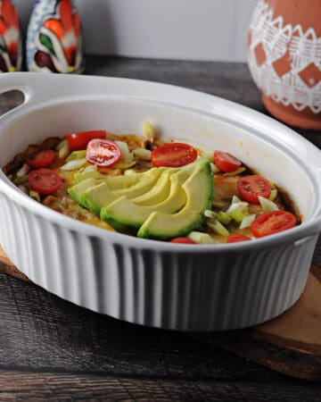 keto taco casserole in an oval dish garnished with green onions, tomatoes and a sliced avocado