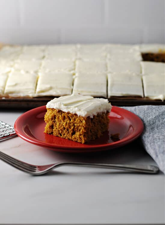 pumpkin bar on a red plate with entire pan of bars behind it