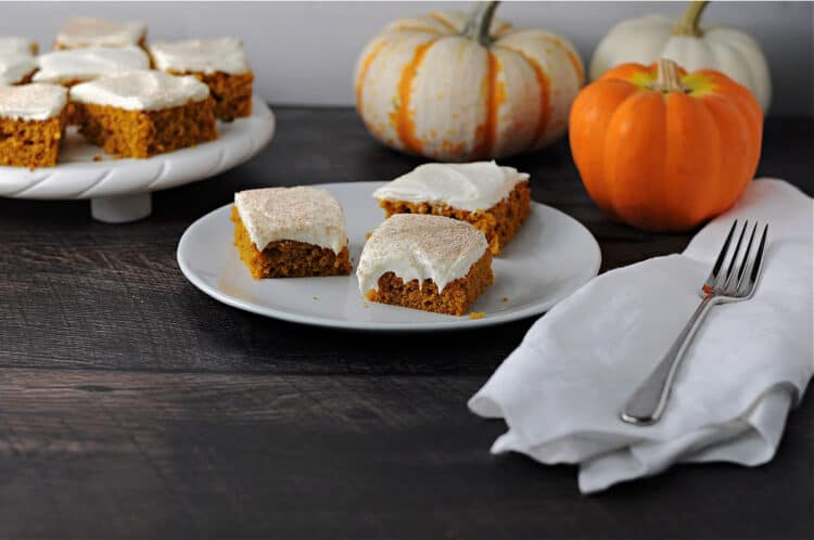 3 pumpkin bars on a plate with more behind
