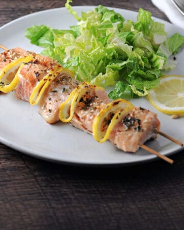 salmon kabob served on a plate with a green salad