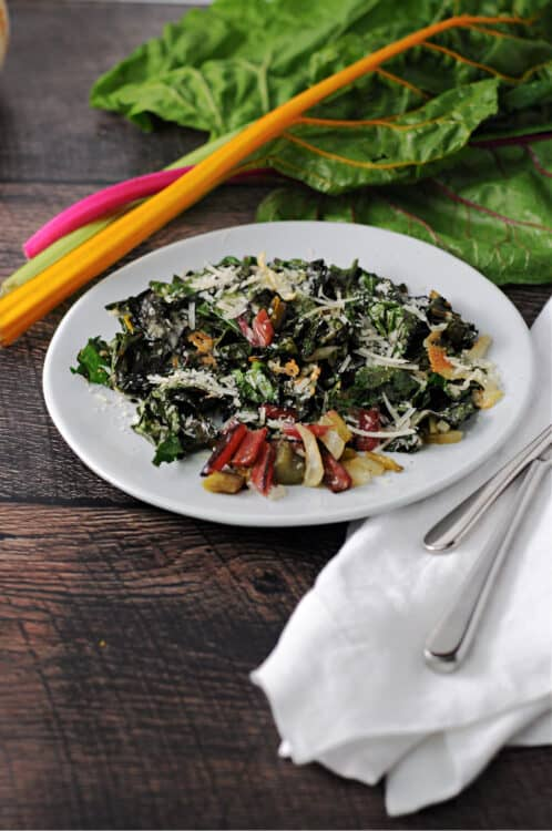 roasted swiss chard on a small white plate with some raw pieces behind